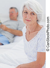 Anxious mature woman sitting in bed while husband is reading...