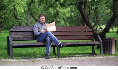Man reads newspaper on bench in the park 1