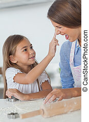 Little girl putting flour on the nose of her mother while...