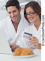 Beautiful couple purchasing online while having breakfast