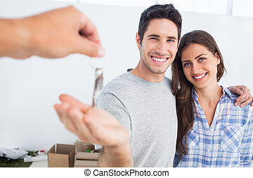 Happy man being given a house key - Happy man next to his...