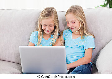 Young twins using a laptop together