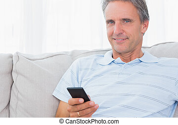 Man relaxing on his couch sending a text smiling at camera...