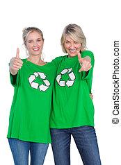 Two women wearing green recycling tshirts giving thumbs up...