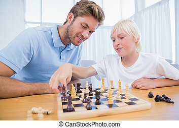 Boy playing chess with his father in the living room
