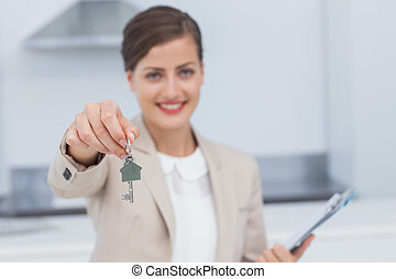 Pretty real estate agent giving house key in a kitchen