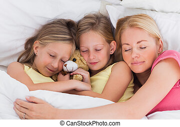 Woman sleeping in bed with her cute children
