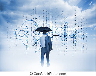 Businessman with an umbrella looking at a giant key with...