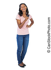 Young woman holding mobile phone with her hand on hip on...