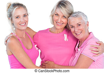 Women wearing pink tops and ribbons for breast cancer on...