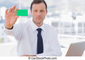 Businessman holding a green business card in his office