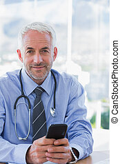 Doctor holding a mobile phone and looking at camera
