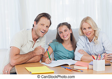 Parents helping her daughter to do her homework