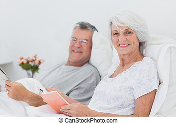 Portrait of a couple reading together in bed