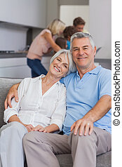 Elderly couple sitting on the couch with their family behind...