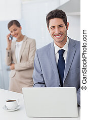 Happy businessman using a laptop before going to work