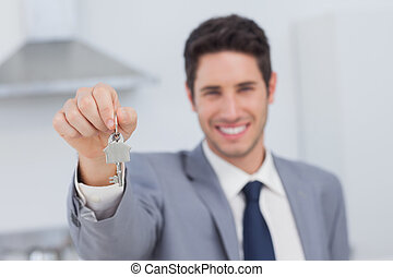 Real estate agent presenting house key in a kitchen