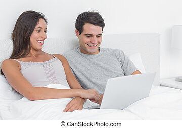 Couple using a laptop together lying in bed in the bedroom