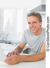 Smiling man using laptop in kitchen