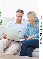 Couple using laptop together on the couch at home in sitting...