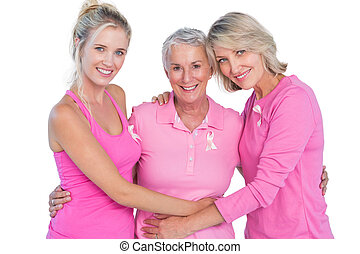 Happy women wearing pink tops and ribbons for breast cancer...