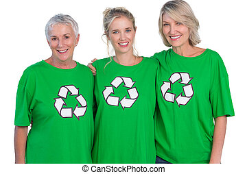 Three women wearing green recycling tshirts smiling at...
