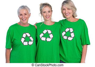 Three women wearing green recycling tshirts smiling at...