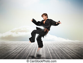 Handsome martial arts fighter over wooden boards leading out...