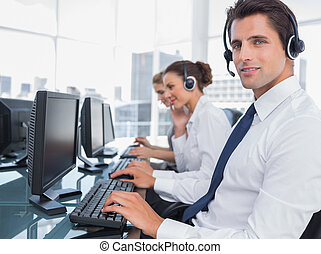 Portrait of smiling call center employee with colleagues...