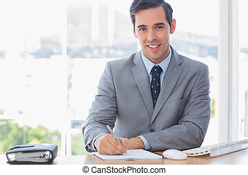 Smiling businessman writing at his desk in the office