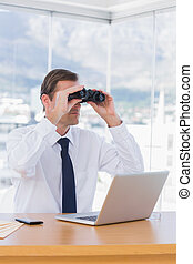 Businessman using binoculars while he is working