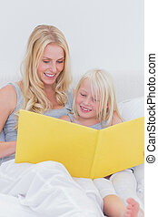 Mother reading a story to her cute daughter