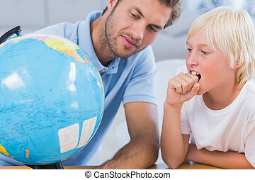 Father looking at globe with his little boy in the living...