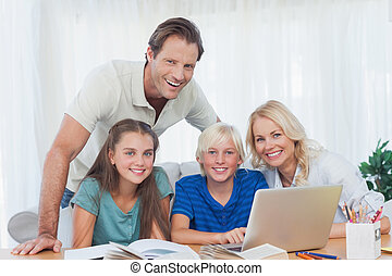 Smiling family using the laptop together to do homework in...