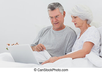 Man with wife pointing at a laptop in bed