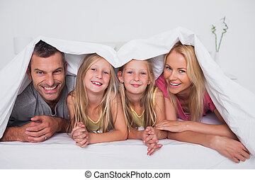 Family playing under the quilt in bed