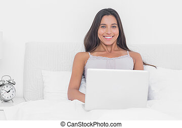 Portrait of an attractive woman using her laptop in bed