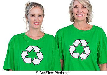 Two women wearing green recycling tshirts on white...
