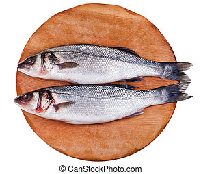 two raw seabass on wooden board isolated on white background