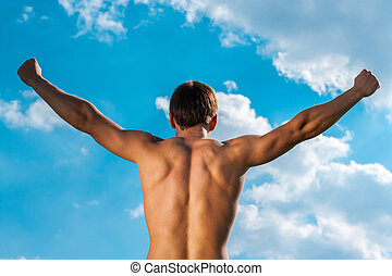 the won person with the raised hands against the sky. view...