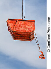 Hanging orange rubble container on build site