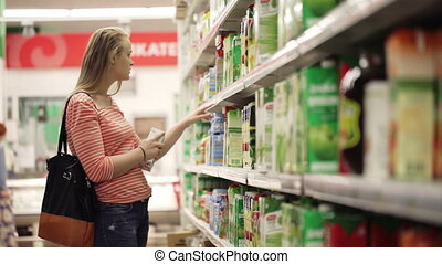 Woman chooses juice in the supermarket