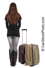 Back view of traveling brunette woman in jeans with suitcase...