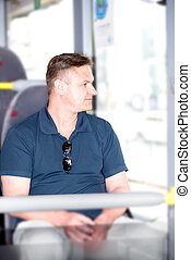 Man traveling on bus and looking through window