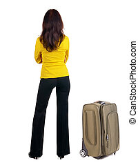 Back view of business woman with suitcase looking up...
