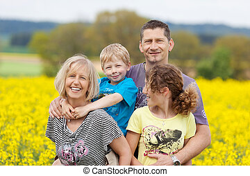 happy family against flower meadow - portrait of a happy...