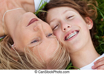 mother and daughter lying close together - close-up view of...