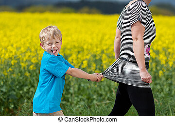 naughty little boy pulling his mom back while walking...