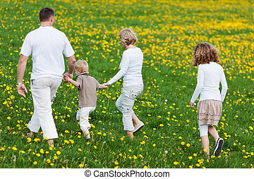 family walking away over grassy field - rear view of a...
