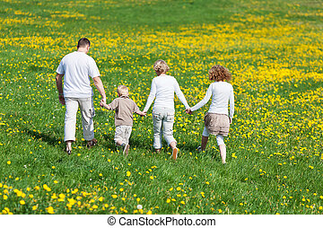 family walking on flower meadow - rear view of a family...